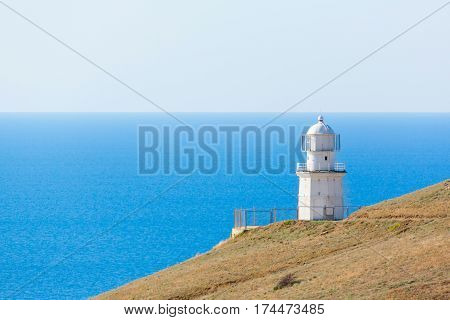 white lighthouse and road on the background of the sea in summer
