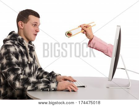 Internet Food ordering and instant Delivery young Man makes Order at Computer Hand of Agent appears from Screen instantly delivering Order holding Sushi Roll wooden Chopsticks on white Background.