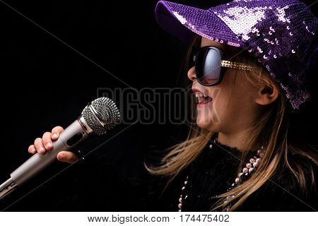 Charismatic Trendy Little Girl Singing Into A Mike