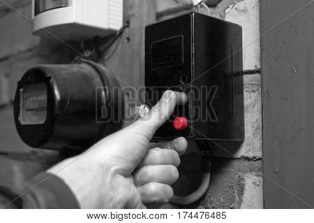 Electrician hand pushing red knob on a fuse box selective color closeup shot