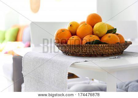 Fresh lemons and mandarin orange fruits on a wicked plate