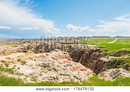 Badlands canyons with green grass and road