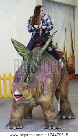 TUCSON, ARIZONA, FEBRUARY 20. The Tucson Expo Center on February 20, 2017, in Tucson, Arizona. A Teenage Girl Rides a Stegosaurus at T-Rex Planet at the Tucson Expo Center in Tucson, Arizona.