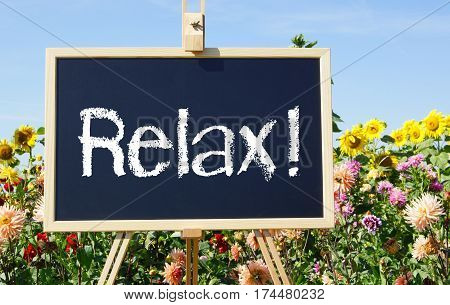 Relax - easel with text in the summer garden