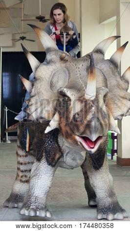 TUCSON, ARIZONA, FEBRUARY 20. The Tucson Expo Center on February 20, 2017, in Tucson, Arizona. A Mother and Son Ride a Styracosaurus at T-Rex Planet at the Tucson Expo Center in Tucson, Arizona.