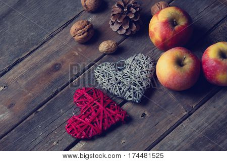 beautiful heart shaped toys cones and nuts on the wonderful brown wooden background