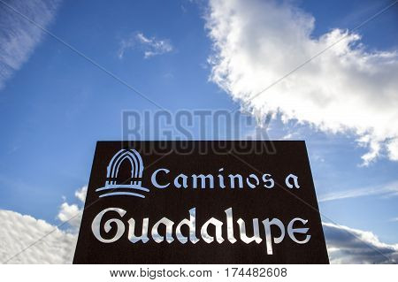 Metal sign post on Guadalupe Pilgrimage way over blue cloudy sky