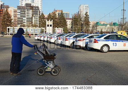 Samara Russia - Nov20 2016: Man with baby carriage and the long line of traffic police cars on city square