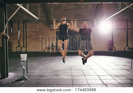 Man And Woman Doing Chin-ups In Gym