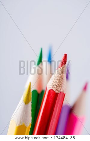 Close up of color pencils with different color over light background. Red pencil stand out other pencils. Drawing and painting. School and education. Artist.