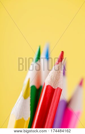 Close up of color pencils with different color over yellow background. Red pencil stand out other pencils. Drawing and painting. School and education. Artist.