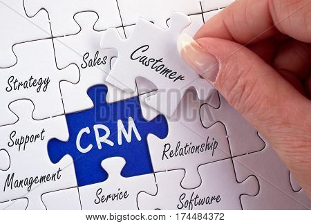 CRM - Customer Relationship Management - hand with business puzzle