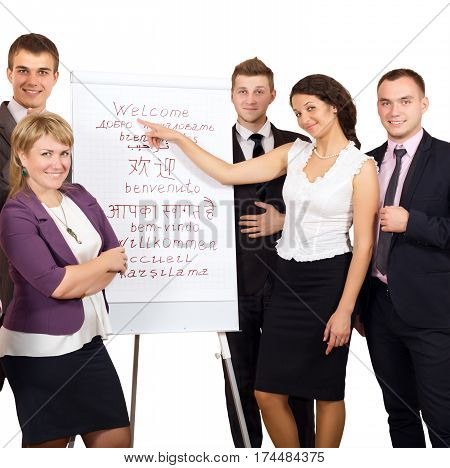 Group of smiling Business People welcoming Customers at flip chart with word WELCOME written in many different Languages on white Background