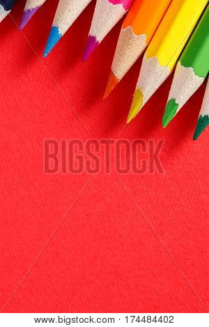 Colored pencils angle. Many different colored pencils on red background. Macro. Close-up view. Art and design. Drawing and painting. Artist.