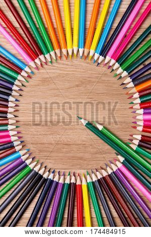 color pencils arranged in a circle on wooden background, top view. Brown table. Two green pencils stand out of other pencils. Art and design. Artist. Drawing and painting.