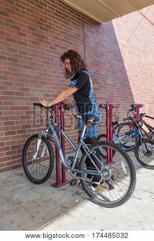 Fairfax USA - February 18 2017: Young woman getting on bike on rack