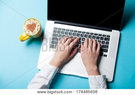 white caucasian female hands typping text on the keyboard near cup of coffee on the wonderful blue background