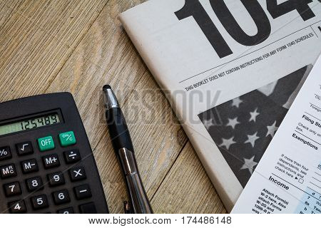Tax preparation with US 1040 form with calculator and pen on wooden board
