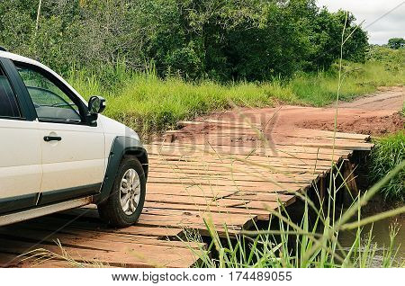 MATO GROSSO DO SUL BRAZIL - FEBRUARY 01 2017: White car passing on a farm bridge in the town of Eldorado. Improvised bridge made of wood that passes over farm river.
