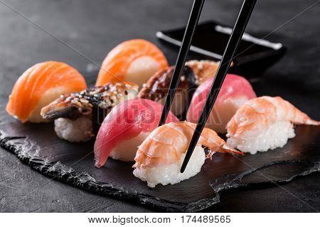 sashimi sushi with chopsticks and soy on black stone slate on dark background