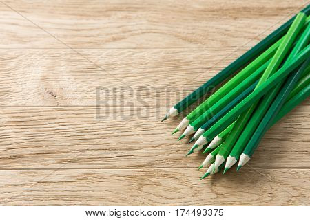 Drawing green pencils on a wooden background. Brown table. Angle position of pencils. Art and design. Drawing and painting. Artist.