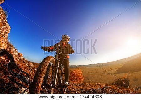 Cyclist man standing on a hill with bicycle and enjoying landscape on a sunny day against a blue sky. Man with white helmet, red backpack and in the black sunglasses. Travel in the countryside. Spring season. Wisheye. Detail of the cycle. Wheel.