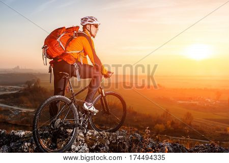 Cyclist with mountain bike on top observing the view. At sunset with lens flare. Beautiful landscape with sunset, hill and rocks. Man with backpack, helmet and in the sunglasses.