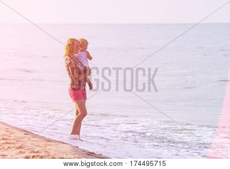 Mother and daughter playing on the beach. Bright holyday mood. Concept of happy family.