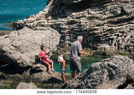 AGHIOS PAVLOS, CRETE, GREECE - JULY 2016: Old man is catching fish together with his young grandsons.