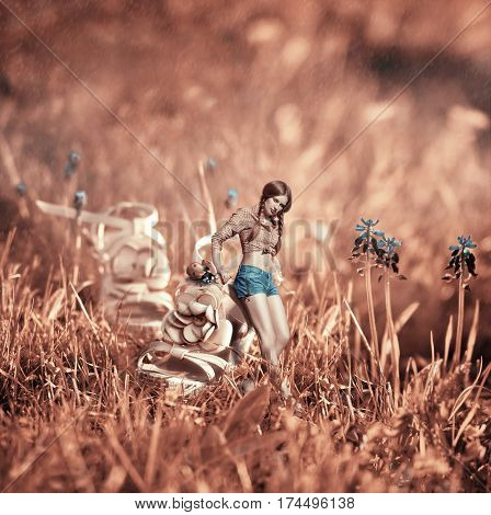 Creative surreal rose toned photo manipulation with a beautiful girl near the giant shoe and ladybug in the middle of a grass field with blue flowers at a sunny day of spring