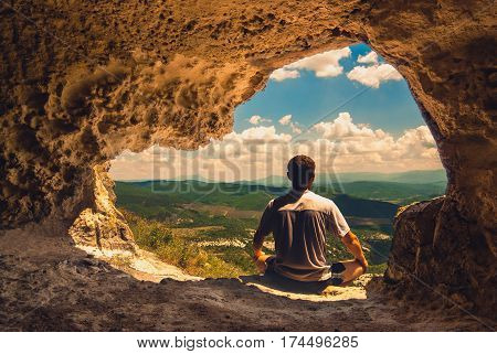 The man who meditates in a cave overlooking the mountain valley