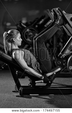 Sportive woman using weights press machine for legs at the gym. Pretty brunette exercising in a simulator. Working her quads at machine. Black and white.