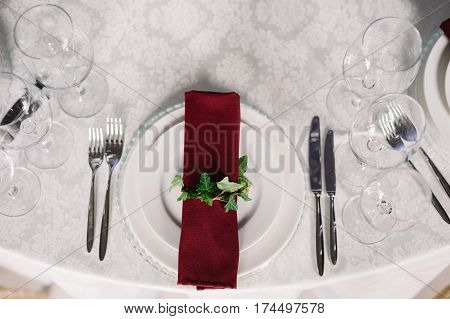 Wedding table decoration of the vinous napkin on the plate for the guests