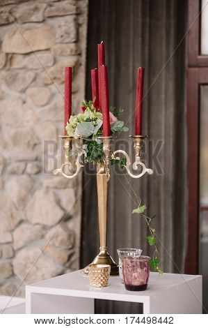 Wedding decorated candlestick with the vinous candles in the greenery