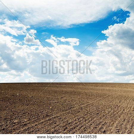 agricultural black plowed field and blue sky with clouds