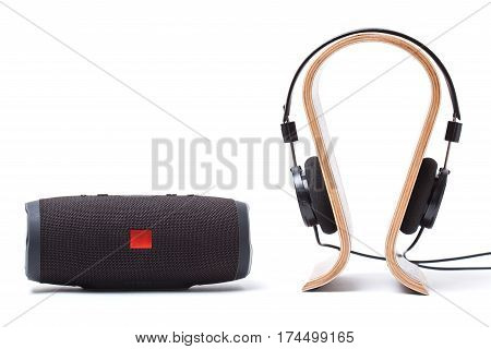 headphones in black and wireless portable speaker system on a white background. isolated