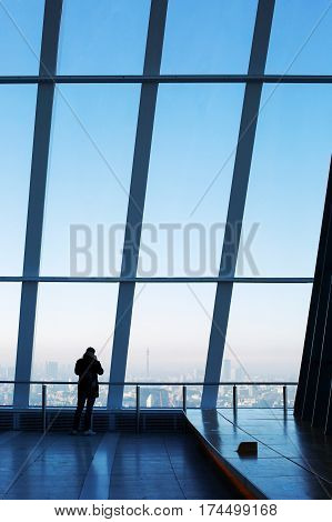 LONDON, UK - DECEMBER 29, 2016: Young man standing by the window in the Sky Garden, the highest public garden in London, taking pictures of the city skyline on mobile phone.