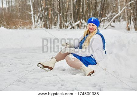 Plump smiling woman in skates sits in snowdrift at outdoor skating rink in winter park.
