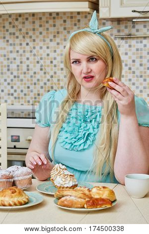 Plump woman sits eating homemade baked sweets at table in kitchen.