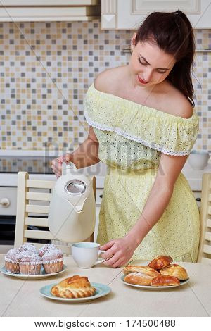 Young woman in yellow dress pours boiling water from kettle into cup on table at kitchen.
