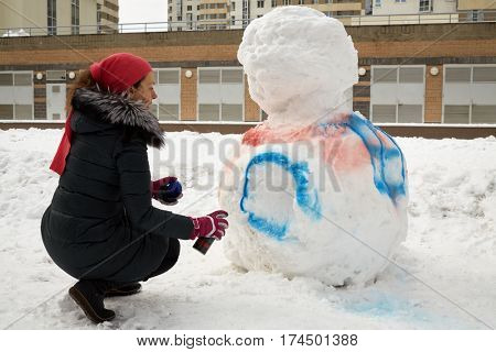 Young woman paints body of snowman with aerosol spray in courtyard of residential buildings.