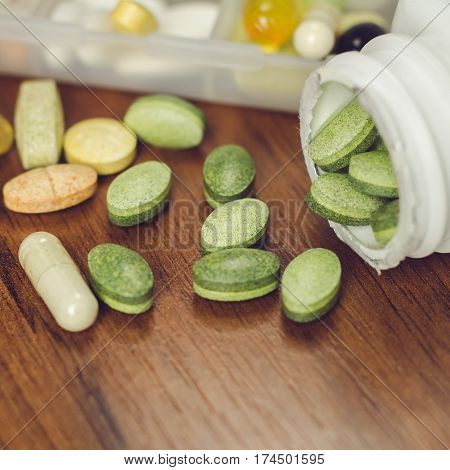 Mixed natural food supplement and vitamin pills on wooden table and in the bottle