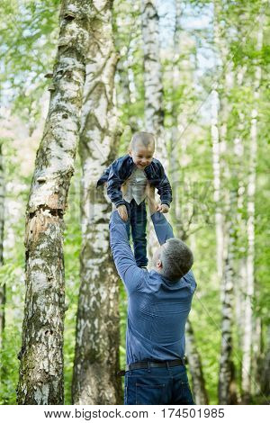 Father plays with little son throwing  him up in summer park.