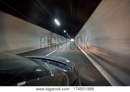 View at illuminated tunnel from right side of moving car.