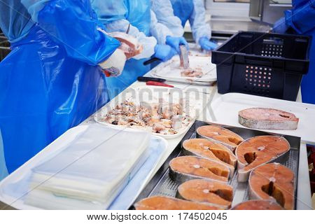 Workers clean pieces of frozen salmon in work shop of factory.