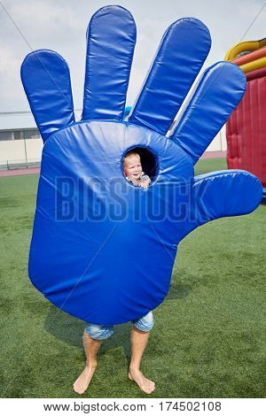 Little boy looks into the hole of big blue hand suit from which male legs protrude.