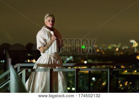 Young woman in white dress and fur mantle stands on high-rise building roof in the night.