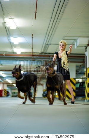 Running blonde with two pulling Doberman on leashes in the underground parking