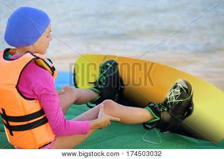 Girl in a lifejacket with a board on her feet sitting on pier near a pond, focus on the hand