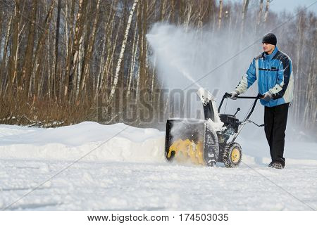 Man removes snow with gas snow thrower at winter day.